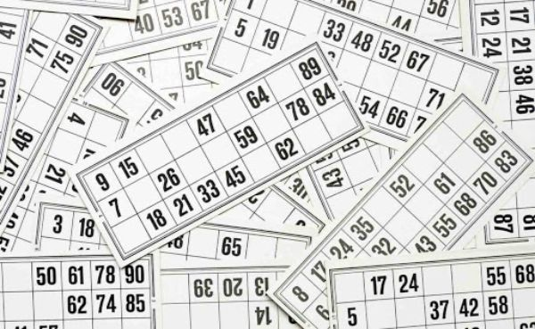 Black and white 90-ball 9x3 bingo cards scattered on top of each other