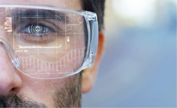 Closeup of a man wearing futuristic augmented reality glasses watching a holograph