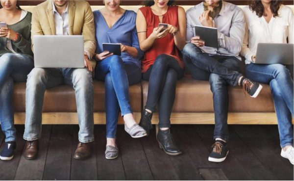 Front view of diverse people sitting on long bench on different technological devices