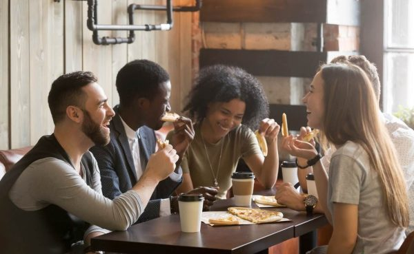 Group of young friends laughing eating pizza and drinking coffee around a table