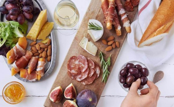 Hands getting an olive, with a cured meat charcuterie selection on white table