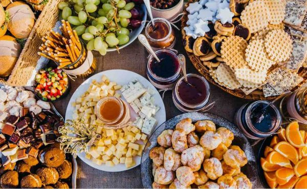 Flatlay of a colourful finger food buffet of cheeses, spreads, fruit and crackers