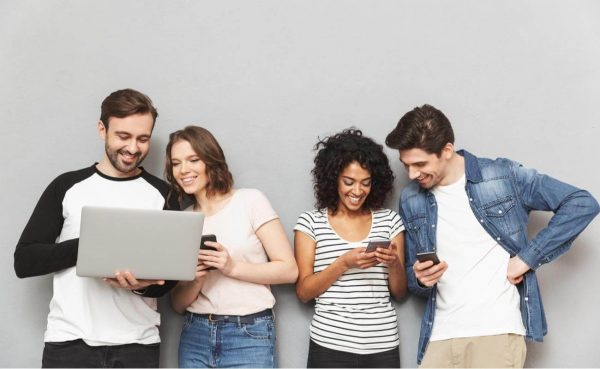 Group of friends holding laptop and mobile phones standing isolated over grey wall background chatting