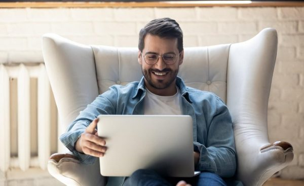 Smiling man relaxing in an armchair playing on a laptop