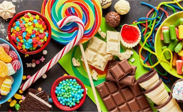 An assortment of colourful sweets and candy scattered on a table