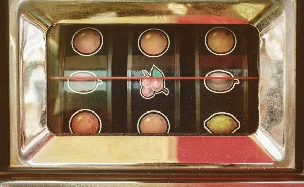 Retro styled image of a vintage gaming slot machine with fruit icons