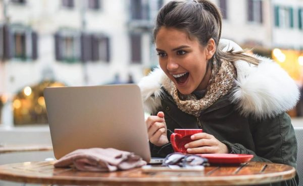 Young woman sitting outside a cafe wearing a coat, drinking coffee and celebrating online win while looking at laptop