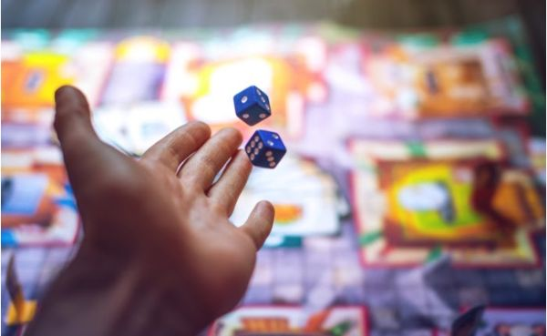 Hand throws the dice on background of colourful blurred board games