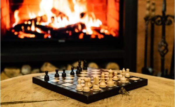 A chessboard on a table in front of a fireplace