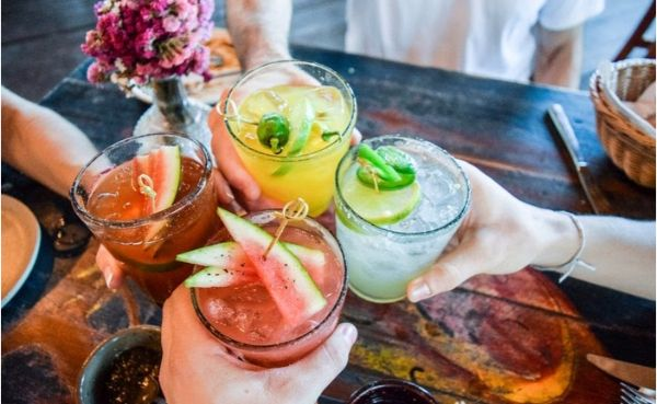 Friends toasting tropical with colourful cocktails