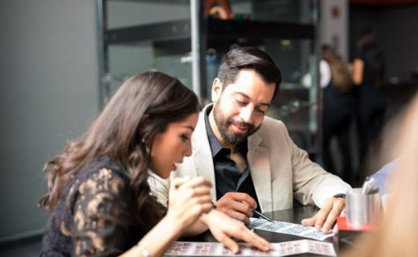 A young man and woman playing bingo in the office