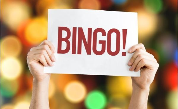 """Hands holding up """"bingo!"""" sign against colourful blurred background"""