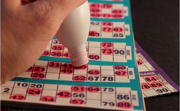 A Bingo Player Using a Red Dauber/Dabber to Mark Off Numbers on a Bingo Card