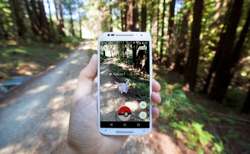 A Player Holds Up A Phone In the Forest With Pokémon Go on the Screen