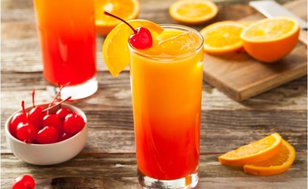 Tequila sunrise cocktail, a bowl of cherries and sliced oranges on wooden table