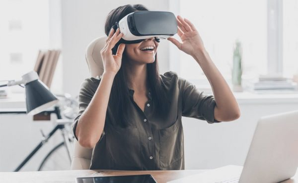Young woman adjusting her virtual reality headset and smiling while sitting at a desk