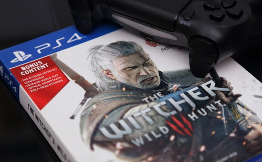 The Cover of The Witcher 3: Wild Hunt Game With a PS4 Remote