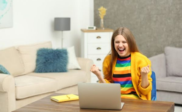Young woman celebrating winning bingo on her laptop at home