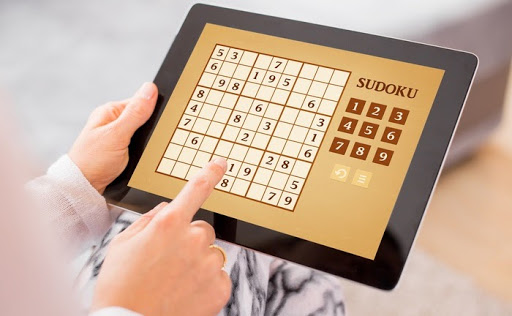 Close-up of a woman playing sudoku on a tablet