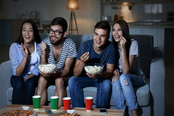 Group of friends eating popcorn and watching a movie at home on the couch