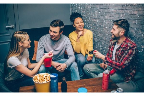 Group of friends hanging out in apartment with popcorn and drinks