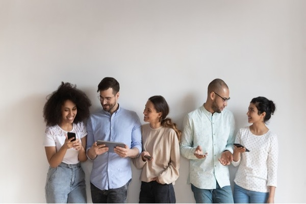 Group of friends standing against a wall using different mobile devices