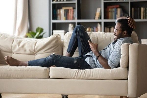 Man lying comfortably on the couch scrolling through mobile phone