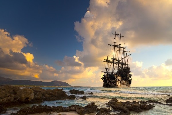 Pirate ship sailing in the ocean at sunset
