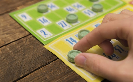 Woman lays a counter on a bingo card to cover a number that's just been called