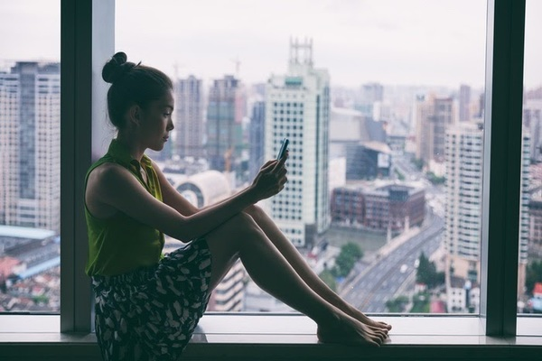 Lonely woman sitting on windowsill overlooking city while on mobile phone