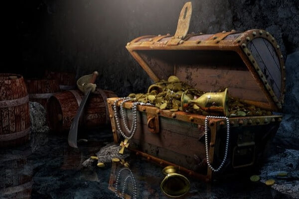 Vector illustration of a pirates treasure chest in a dark cave filled with gold and gems