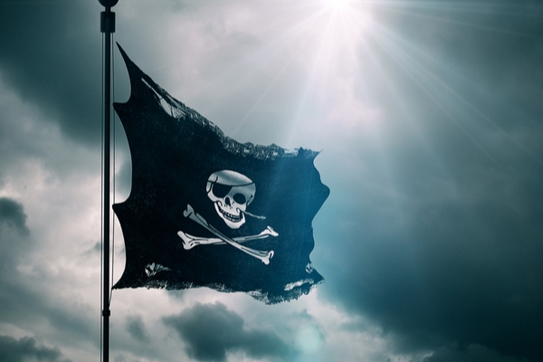 A pirate flag flies against a dark and stormy sky