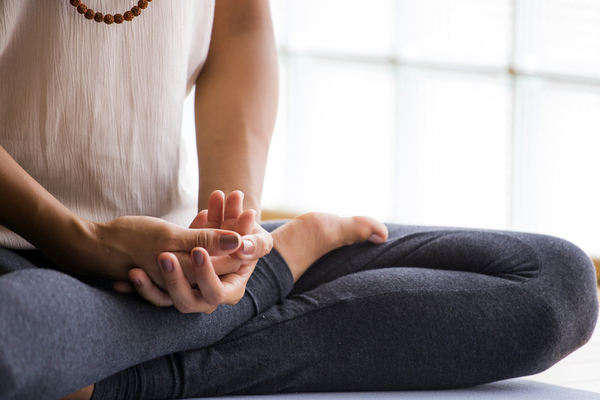 A woman sits with her hands and legs crossed while she meditates.