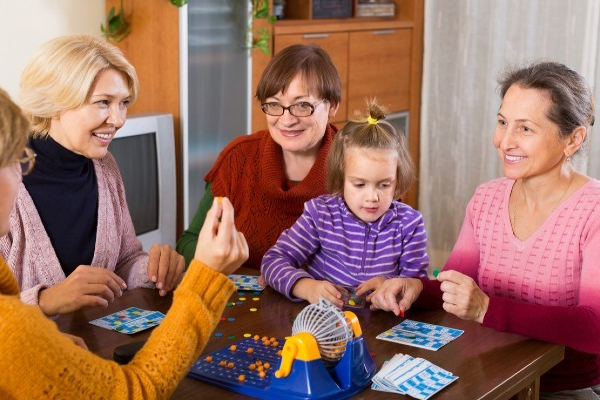 Four women sitting around a table with a child playing bingo.