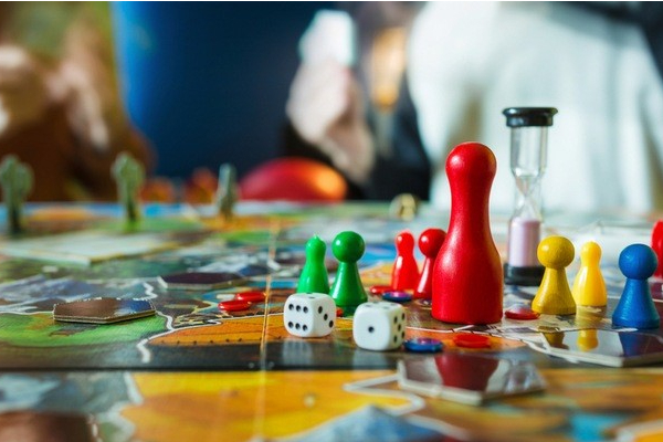 Table-level view of a board game with colourful pieces, dice and a sand timer.
