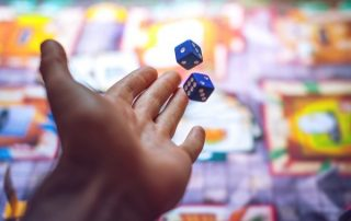 Close-up of a player's hand throwing two blue dice onto a board game.