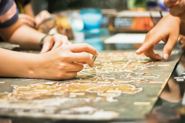 People playing a board game with one person holding a chip and the other pointing at the map on the board.
