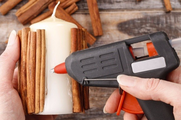 Woman holding cinnamon sticks, a candle and glue gun doing a DIY project.